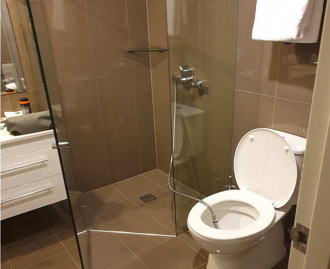 White toilet with illegal hose running from adjacent shower